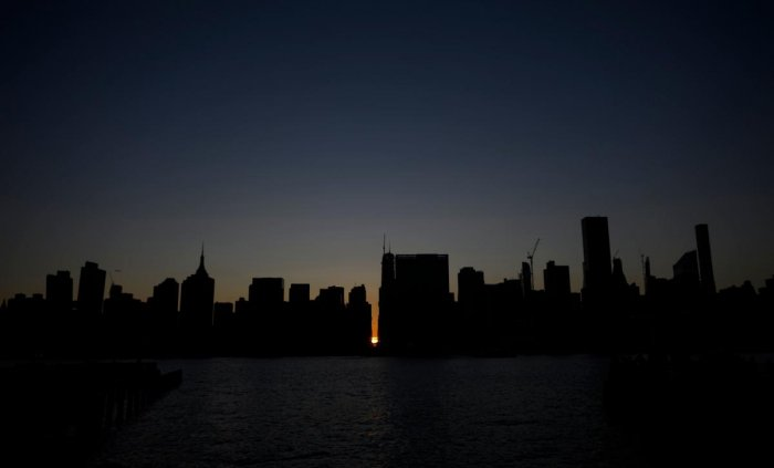The sun sets behind 42nd Street in Manhattan during a power outage in New York City on July 13, 2019. - Subway stations plunged into darkness and the billboards of Times Square suddenly flicked off as New York's Manhattan was hit by a power outage on Satu