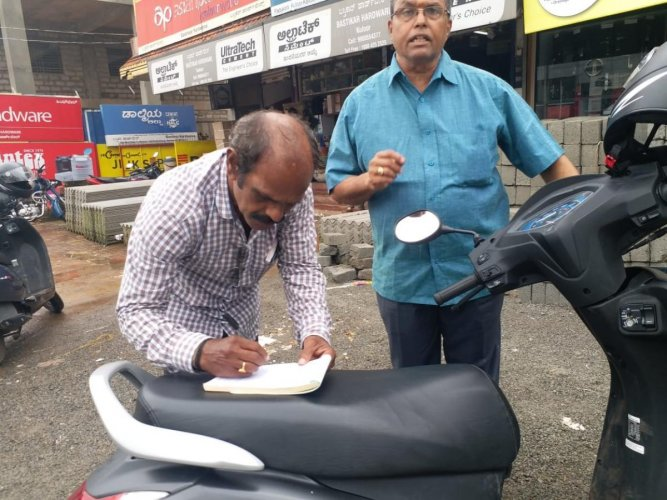 Officials of Mangaluru City Corporation collect fine from those who had dumped waste on the road in Mangaluru.