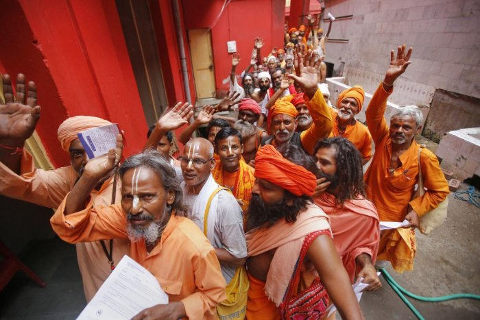 Pilgrims chant religious slogans as they stand in a queue to get themselves registered for Amarnath Yatra, at Ram Mandir base camp in Jammu, Friday, July 12, 2019. (PTI Photo)