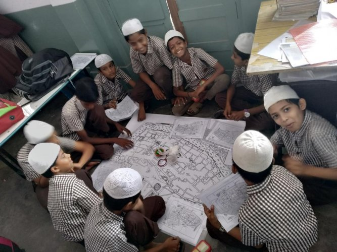 Students at the RMES School find places in an old map of Bengaluru city as part of an activity organised by Intach. Special arrangement