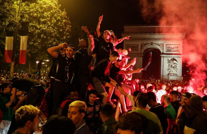 Algeria supporters celebrate after Algeria won the 2019 Africa Cup of Nations (CAN) semi-final football match against Nigeria, on the Champs-Elysee avenue in Paris on July 14, 2019. - Riyad Mahrez rifled in a stoppage-time free-kick to earn Algeria a dram