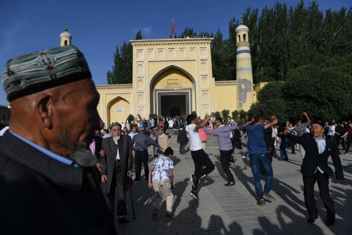 This photo taken on June 5, 2019 shows Uighur men dancing after Eid al-Fitr prayers, marking the end of Ramadan, outside the Id Kah mosque in Kashgar, in China's western Xinjiang region. - In China's Xinjiang, a northwest region tightly controlled by poli