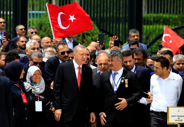 Turkish President Tayyip Erdogan visits a monument as he is flanked by his supporters during a ceremony marking the third anniversary of the attempted coup, at the Presidential Palace in Ankara. (Reuters Photo)