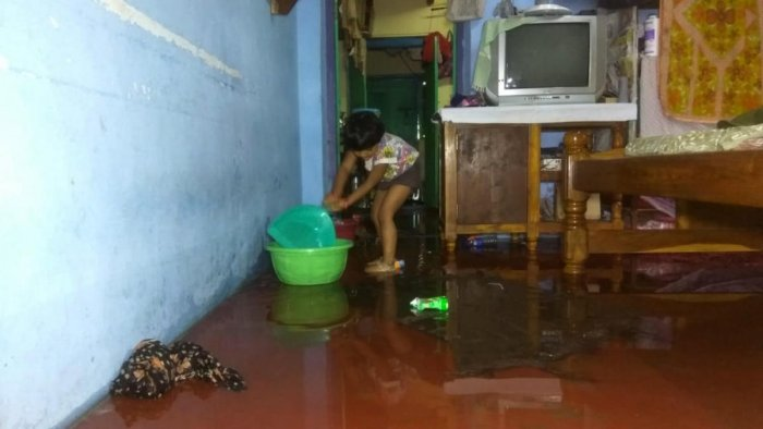 A child drains out water after Sunday night showers flooded her house at Madhavnagar in Karwar.