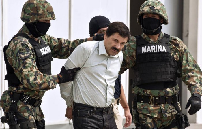 Mexican drug trafficker Joaquin Guzman Loera aka 'El Chapo Guzman' (C), is escorted by marines as he is presented to the press in Mexico City in 2014 (AFP File Photo)