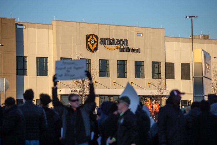 Demonstrators shout slogans and hold placards during a protest at the Amazon fulfillment center in Shakopee, Minnesota last year (AFP File Photo)