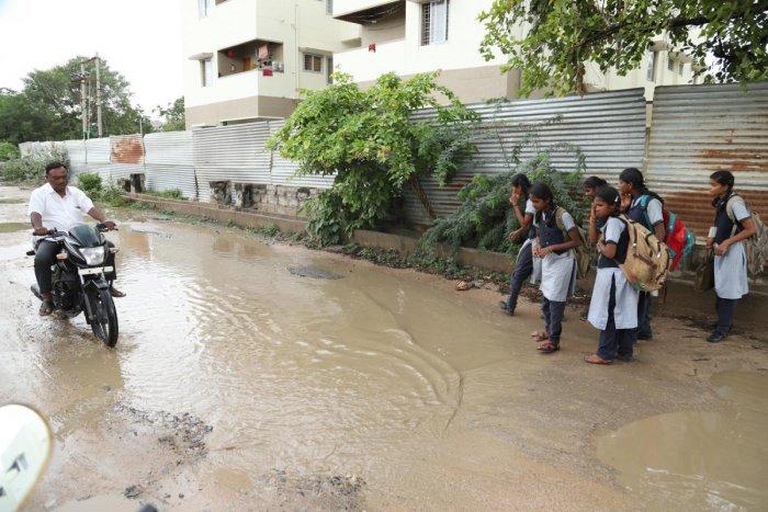 Tuesday afternoon showers render the pothole-ridden SP Office-Lal Bahadur Shastri Nagar road in Raichur slushy. The city received its first proper monsoon rain of the season. (Right) River Tungabhadra in full flow in Harapanahalli taluk of Ballari distric