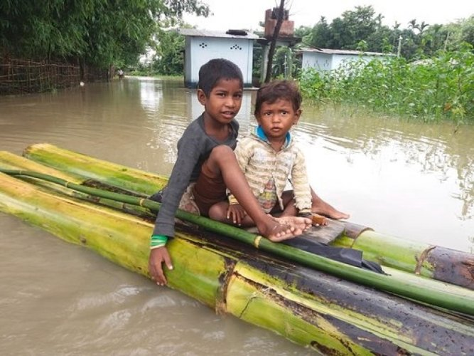 Two flood-hit children in a raft in Dhemaji district in Assam on Monday. Photo credit: Save the Children.
