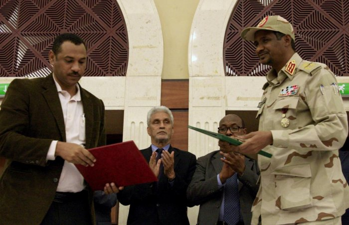 Sudanese deputy chief of the ruling miliary council Mohamed Hamdan Dagalo (R) and protest movement Alliance for Freedom and Changes leader Ahmad al-Rabiah stand after inking an agreement. Photo credit: AFP