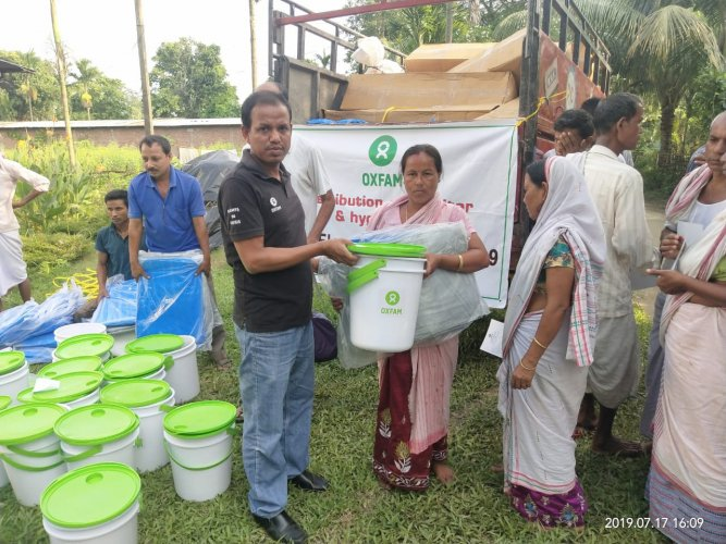 Oxfam India distributing relief materials among flood hit people in Lahorighat area in upper Assam on Wednesday. DH photo