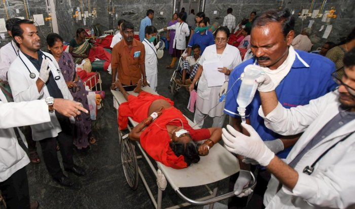 A woman is shifted to a hospital in as she complained of sickness after consuming 'prasad' at Maramma temple in Chamrajanagar district, in Mysuru, Friday, Dec 14, 2018. At least five people died and 40 others fell sick due to suspected food poisoning after consuming 'prasad' at the temple. (PTI Photo)