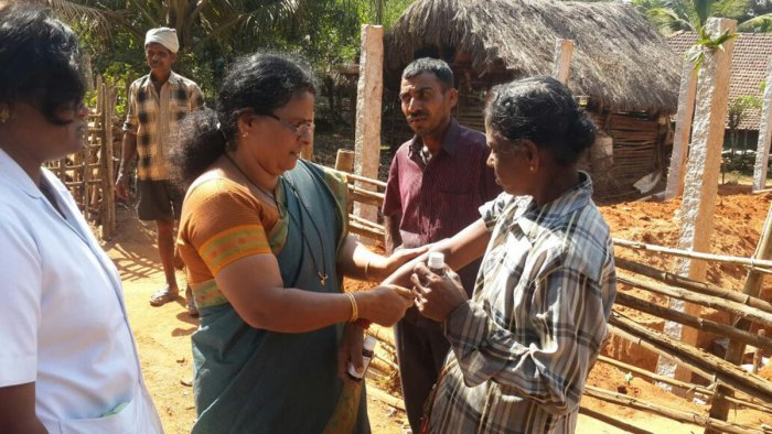Health officials applying DMP oil to villagers in one of the villages of Thirthahalli taluk in Shivamogga district.