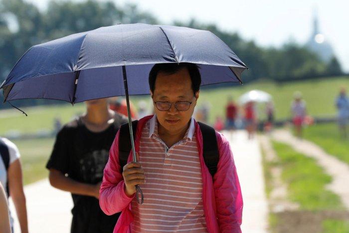 A tourist holds an umbrella as he walks at the National Mall near the Washington Monument in Washington, DC, U.S., June 27, 2019. REUTERS/Yuri Gripas