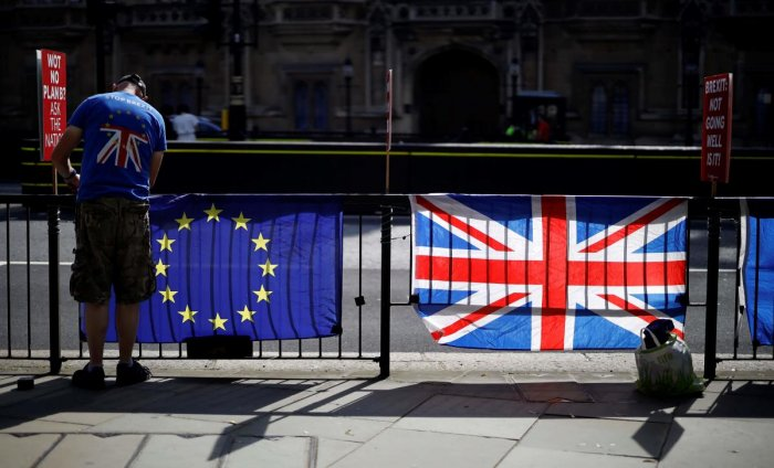 An anti-Brexit activist secures an EU flag to a railing opposite the Houses of Parliament in Westminster, central London on July 2, 2019. (AFP)