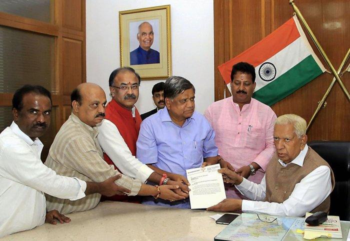 BJP leaders Jagadish Shettar (C), Arvind Limbavali (3rd L) and others submit a letters to Karnataka Governor Vajubhai Vala (R) during a meeting at Rajbhavan, in Bengaluru on Thursday. PTI photo