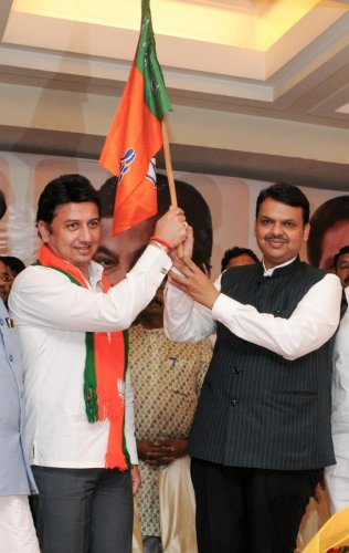 Maharashtra Chief Minister Devendra Fadnavis and former NCP MP Ranjitsinh Mohite Patil hold the BJP flag after the latter joined the party, in Mumbai on March 20, 2019. PTI