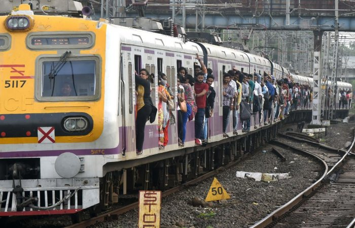 A crowded local passenger train approaches a platform in Mumbai on July 5, 2019. (Photo: AFP)