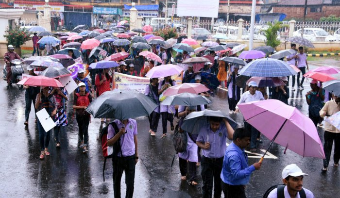 College students take part in a rally, amid rain, organised as a part of 'Swasthya Sankalpa' campaign on the premises of the Town Hall, Mangaluru, on Thursday.
