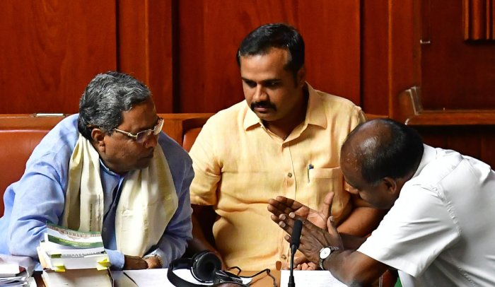 Congress Legislature Party leader Siddaramaiah speaks to Chief Minister H D Kumaraswamy in Legislative Assembly on Thursday. Chief Whip of the government Ganesh Hukkeri looks on. DH photo