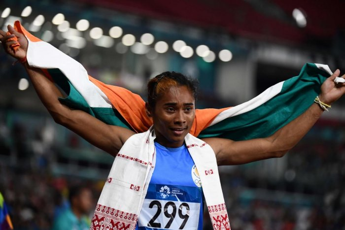 India's Hima Das celebrates winning the silver medal after the final of the women's 400m athletics event during the 2018 Asian Games in Jakarta on August 26, 2018. (Photo by Jewel SAMAD / AFP)