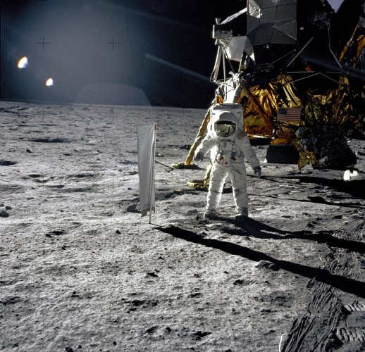 """Moonscaped: Astronaut Edwin E. Aldrin, Jr., Lunar Module pilot, is photographed during the Apollo 11 extravehicular activity (EVA) on the lunar surface. In the right background is the Lunar Module """"Eagle."""" On Aldrin's right is the Solar Wind Composition (SWC) experiment already deployed. This p hotograph was taken by Neil A. Armstrong with a 70mm lunar surface camera. (NASA)"""