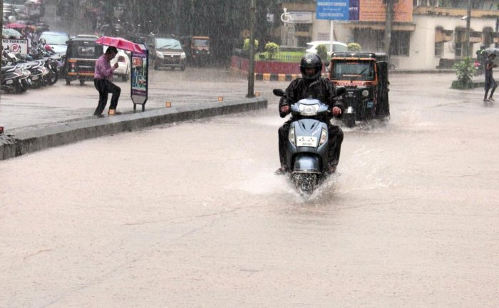 Vehicles wade through the flooded road near City Hospital in Mangaluru on Friday.