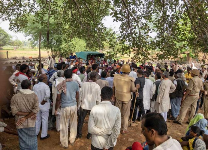 Villagers gather at the site where 10 people were gunned down over a property dispute in Sonbhadra district. (PTI Photo)