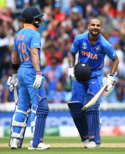 India's Shikhar Dhawan (R) celebrates after scoring a century (100 runs) alongside India's captain Virat Kohli (L) during the 2019 Cricket World Cup group stage match between India and Australia at The Oval in London on June 9, 2019. (Photo by AFP)