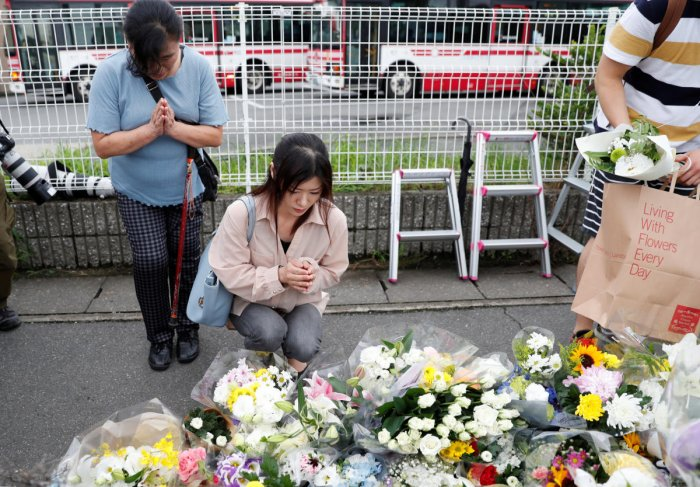Women pray outside the Kyoto Animation building which was torched by arson attack, in Kyoto, Japan, July 19, 2019. REUTERS/Kim Kyung-Hoon