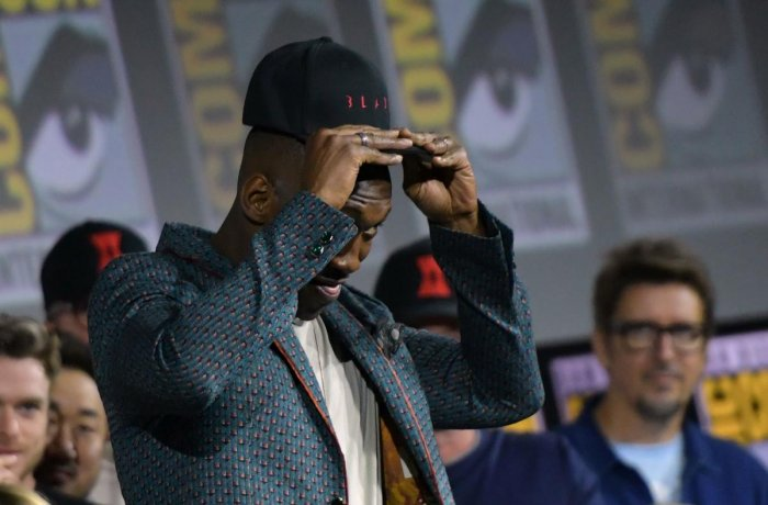 """US actor Mahershala Ali puts on a """"Blade"""" hat on stage during the Marvel panel in Hall H of the Convention Center during Comic Con in San Diego, California on July 20, 2019. AFP"""