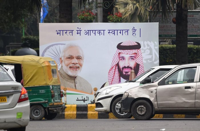 Vehicles drive past a billboard displaying the portrait of Indian Prime Minister Narendra Modi and Saudi Arabian Crown Prince Mohammed bin Salman ahead of his official visit to India, in New Delhi on February 19, 2019. (AFP)