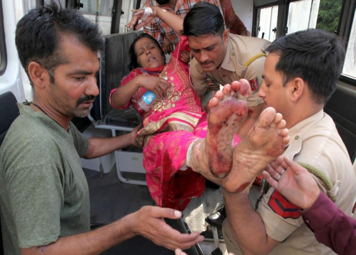 Volunteers and police personnel carry Sulakshana Devi, who was injured in cross border firing between Indian and Pakistan, into the Government Medical College Hospital in Jammu on Sunday. AFP