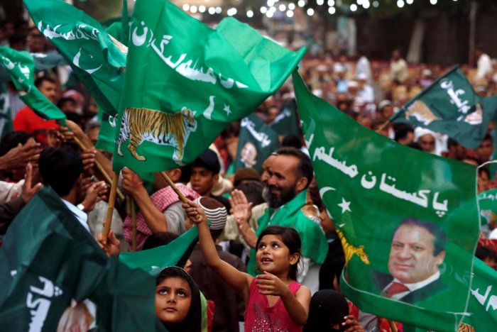 A child supporter of Shahbaz Sharif, brother of ex-prime minister Nawaz Sharif, and leader of Pakistan Muslim League - Nawaz (PML-N) waves party flags with others to welcome him during a campaign rally ahead of general elections in the Lyari neighborhood.