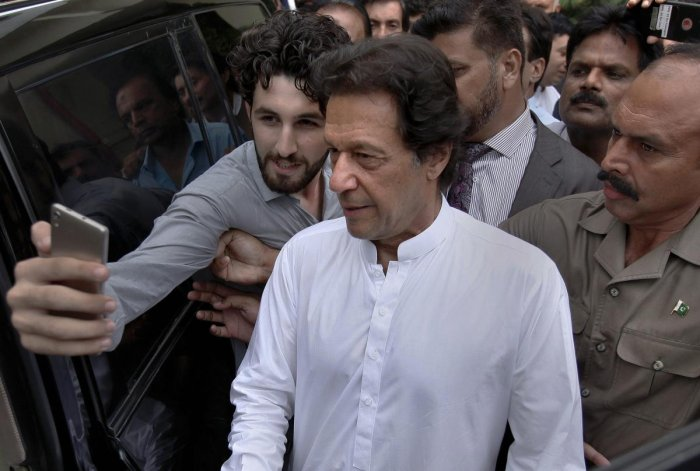 A Pakistani takes selfie with Imran Khan, center, head of the Pakistan Tehreek-e-Insaf party, as he leaves a party meeting in Islamabad, Pakistan, Monday, Aug. 6, 2018. The party won the most parliament seats in last month's general elections and is expected to form a governing coalition later this month. (AP/PTI)