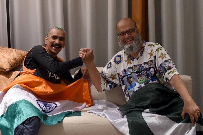 BONDING OVER SPORTS: India cricket fan Sudhir Kumar (left) and Pakistan fan Mohammad Basheer share a laugh. Basheer has sponsored Sudhir's trip to the Asia Cup. AFP