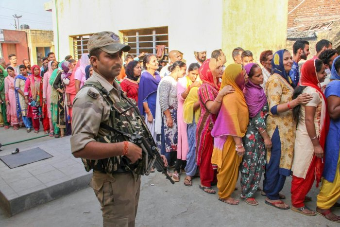 A security person stands guard as people wait in a long queue to cast their votes at a polling station during municipal elections in Bari Brahmana, about 25 kms from Jammu on Saturday. TI