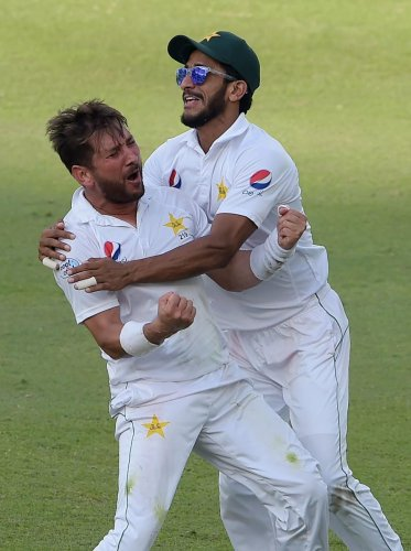 BRILLIANT SHOW! Pakistan's Yasir Shah (left) celebrates with team-mate Hasan Ali after taking the final wicket of New Zealand batsman Trent Boult. AFP