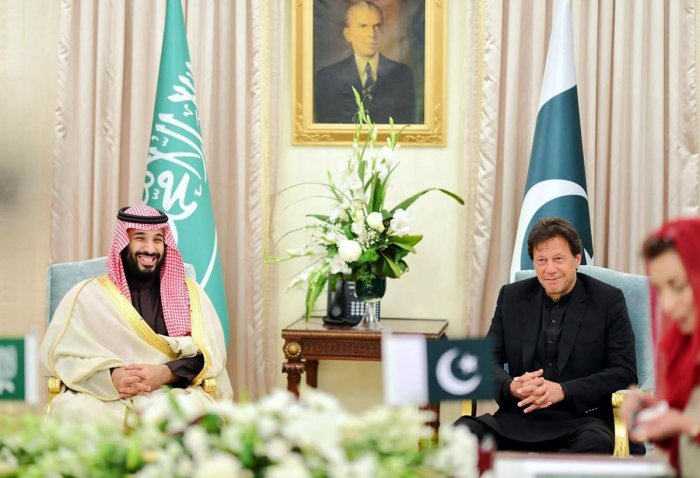 In this handout photograph released by Pakistan's Press Information Department (PID), Pakistan's Prime Minister Imran Khan and Saudi Arabian Crown Prince Mohammed bin Salman smile as they look at their delegation members during a signing of a MOU at the Prime Minister House in Islamabad. AFP/PID/Handout