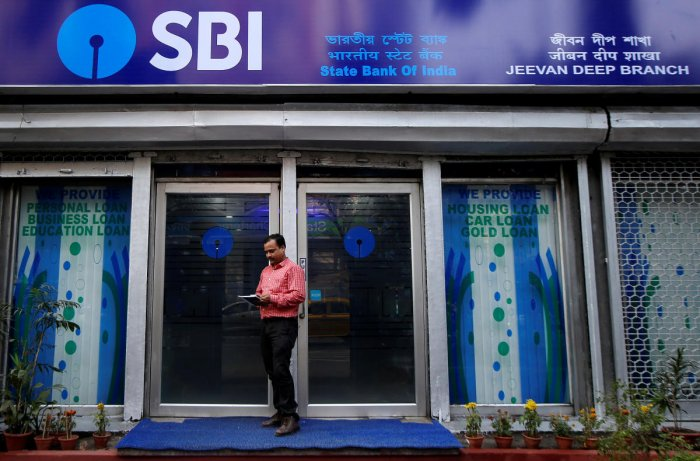 A man checks his mobile phones in front of State Bank of India (SBI) branch in Kolkata. REUTERS