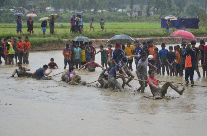 Schoolchildren take part in a tug-of-war competition amid rain at the state-level marshy field sports meet at Kaggodlu in Madikeri taluk on Saturday.