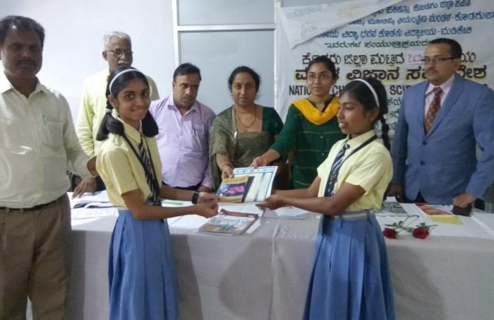 Zilla Panchayat CEO K Lakshmipriya awards the certificate of selection to two of the students selected for the state-level children's science convention organised by Rajya Vijnana Parishat.