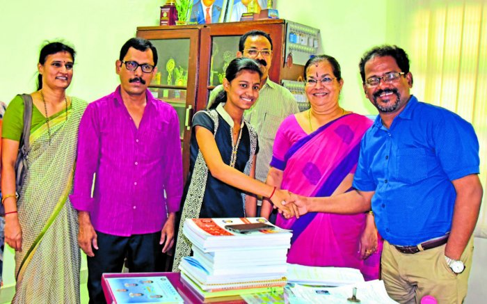 Canara PU College Principal Gopal Shetty wishes Shreya Shenoy, who secured second rank in Commerce in second PU Examination in the state.