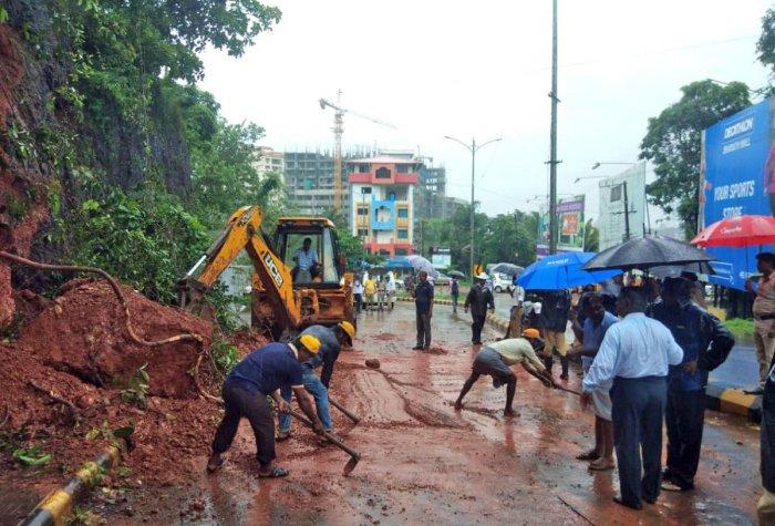 Labourers clear a boulder that fell due to heavy rain at Bejai Battagudda in Mangaluru on Monday.