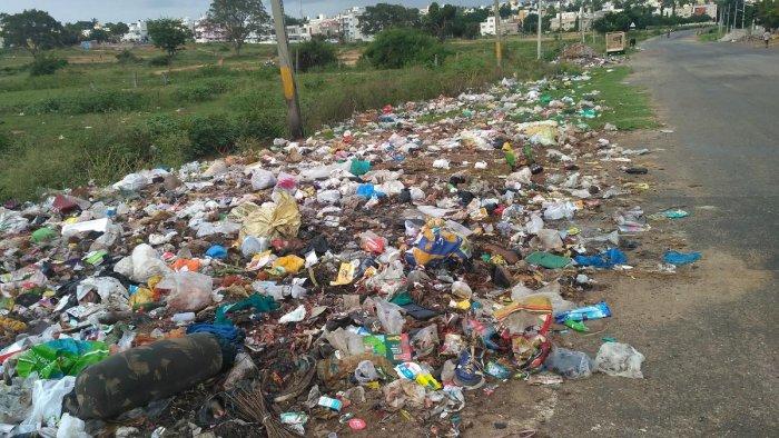 Garbage dumped beside a road, near Vijayanagar Police station, in Mysuru. Dh-file photo
