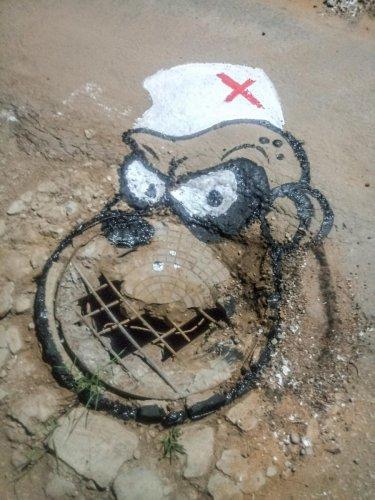 Artist Badal Nanjundaswamy's art work on pothole, at Saraswathipuram Swimming Pool Road in Mysuru in 2017. DH/PV PHOTOS