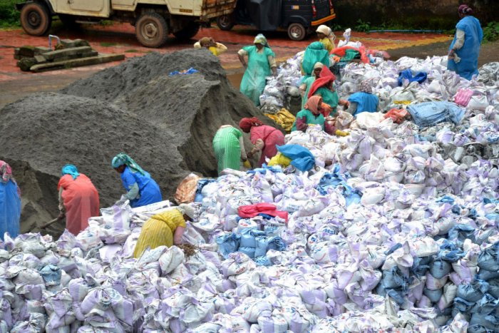 Workers fill sacks with manufactured sand, which will be used at the locations of landslides in Kodagu.