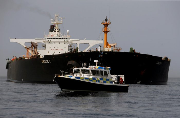 A Royal Gibraltar Police's boat guards the Iranian oil tanker Grace 1 as it sits anchored after it was seized earlier this month by British Royal Marines off the coast of the British Mediterranean territory on suspicion of violating sanctions against Syria, in the Strait of Gibraltar. (Reuters Photo)