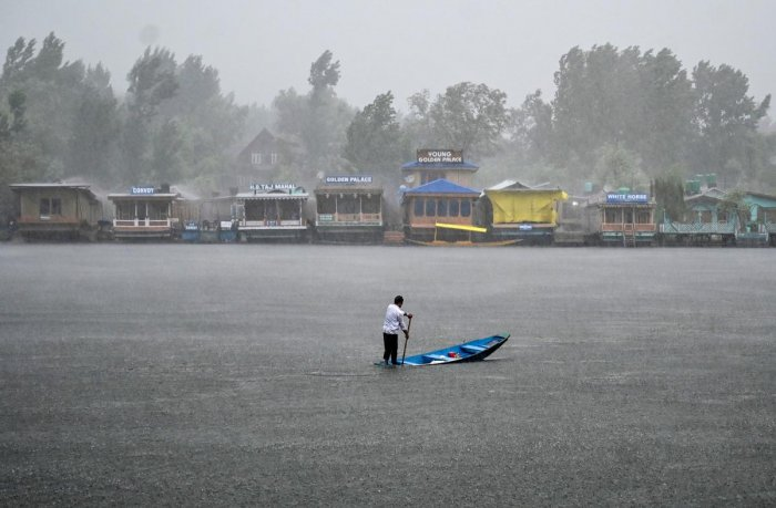 A resident rows a boat on the Dal Lake during a heavy rainfall in Srinagar on July 25, 2019. (AFP)