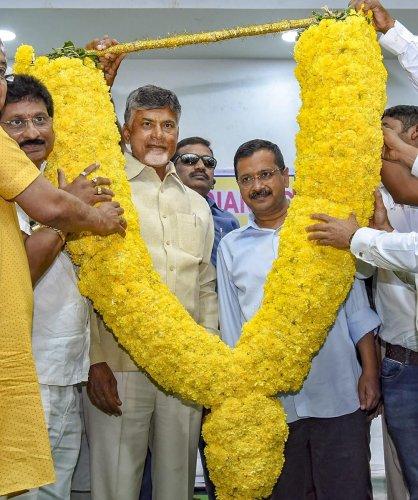 Delhi Chief Minister Arvind Kejriwal and Andhra Pradesh Chief Minister and Telugu Desam Party's Chandrababu Naidu being garlanded by party leaders, in Vijayawada, on Thursday. PTI