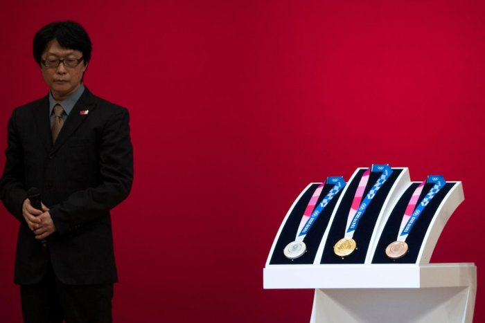 Junichi Kawanishi, the Japanese designer of the Tokyo 2020 Olympic Games medals, stands next to the medals after their unveiling during a ceremony marking one year before the start of the games in Tokyo (AFP Photo)
